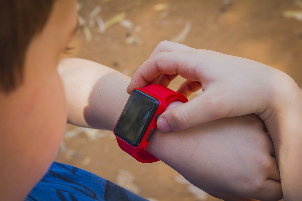 Young boy looking at Smart Watch