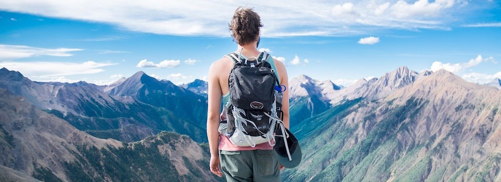 backpacker-looking-at-mountain-landscape