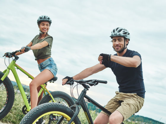 Couple cycling and looking at watch