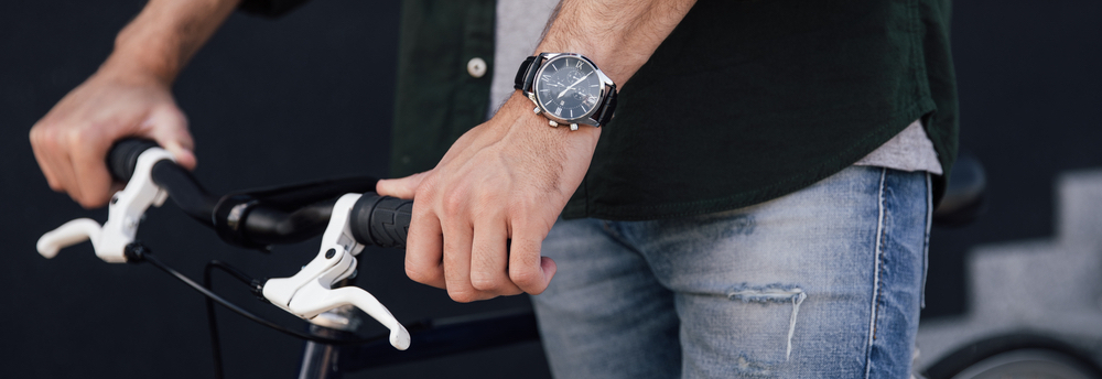 man-holding-bike-with-watch-on