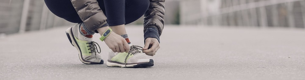 runner-tying-shoes-with-fitness-tracker-on-wrist