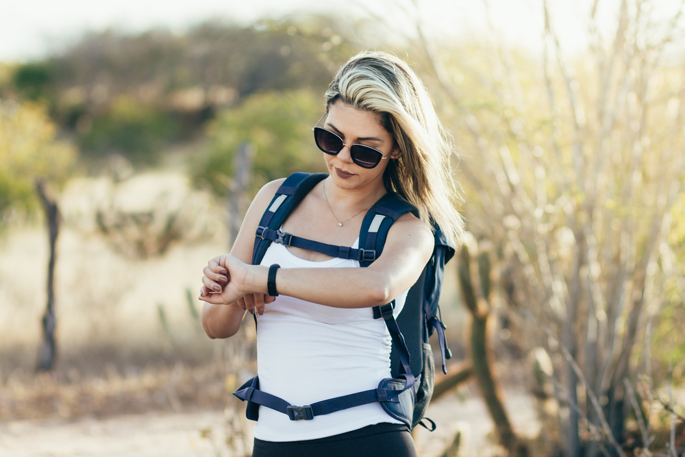 A female Hiker looking at her GPS Watch