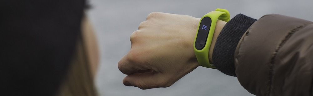 woman-looking-at-green-pedometer-watch