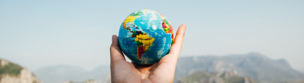 person-holding-small-world-globe
