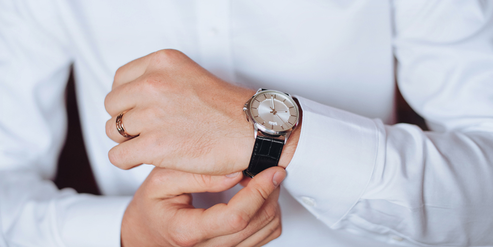 A man in a white shirt is putting on his watch