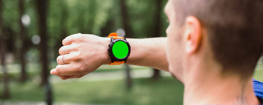 Athlete man looking on smart watch after workout. Watch with chromakey green screen