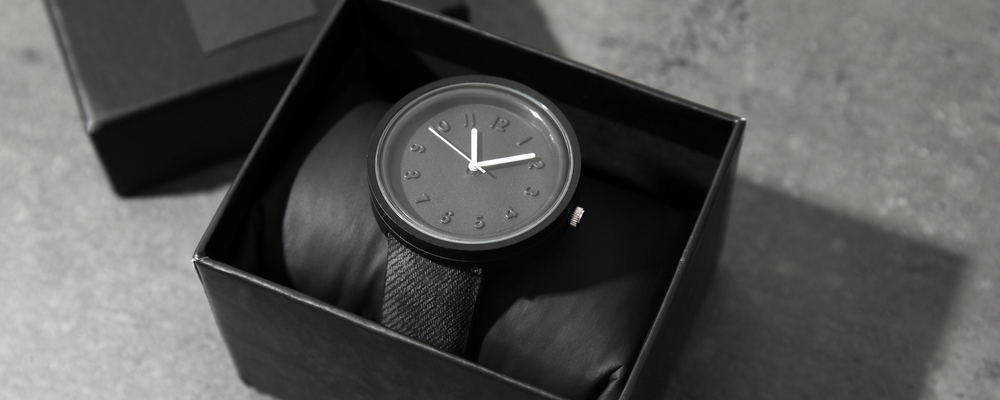 Box with stylish wrist watch on gray table.