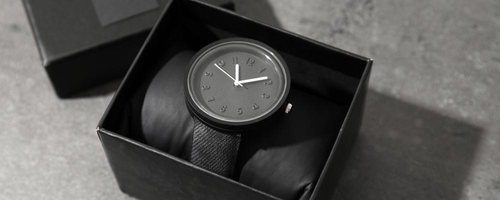Box with stylish wrist watch on gray table.