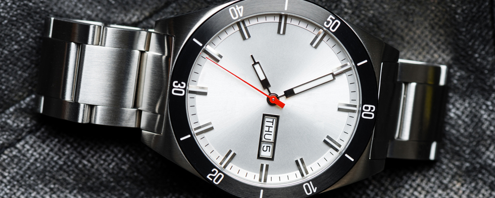 closeup 3 hands luxury men's watch with stainless steel case and bracelet