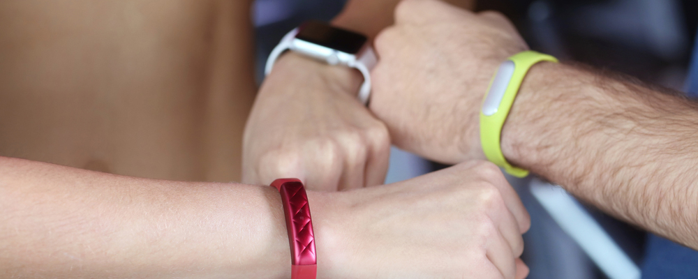 Hands of young people with fitness trackers in gym, closeup