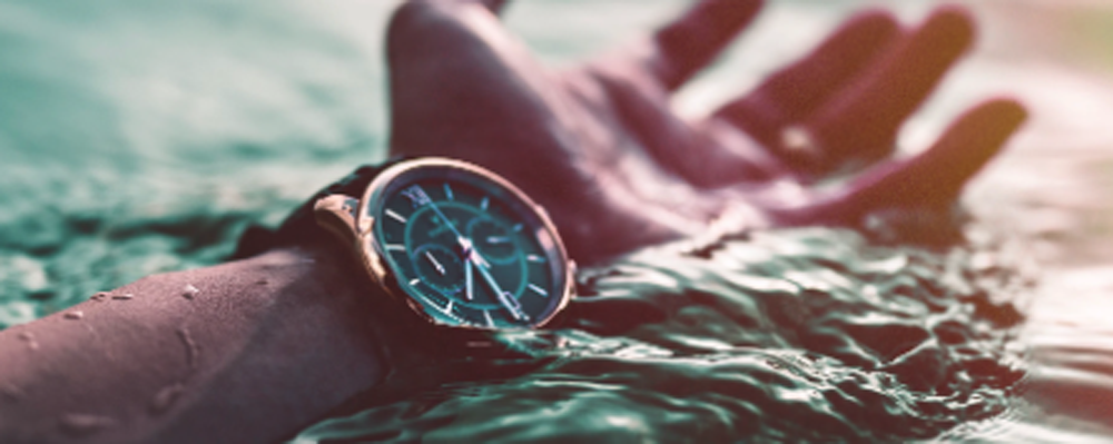Person's hand with wrist watch on the water