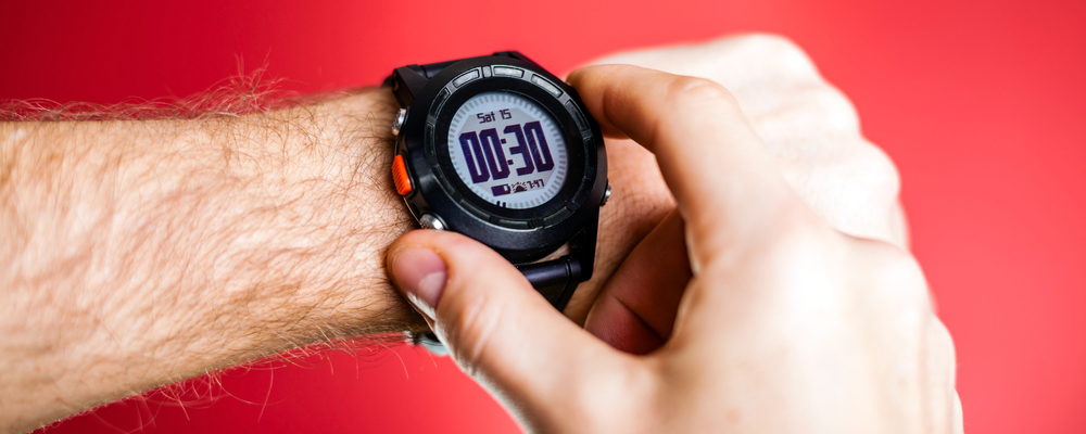 Male runner ready to run with sport watch. Taking puls or checking gps position wristwatch. Man and fitness, exercising concept on red background