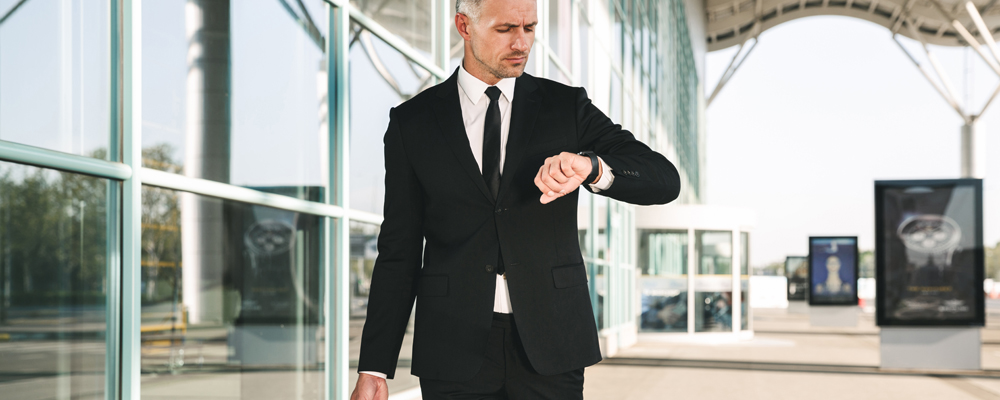 Serious businessman dressed in suit walking with a suitcase outside airport terminal and looking at his wristwatch