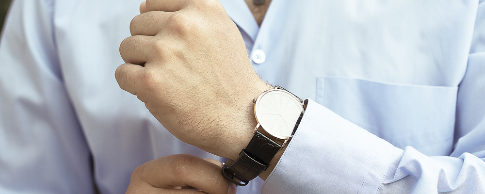 the man in the light blue shirt wears a luxary watch