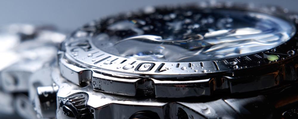 Closeup of wet metal wrist watch.