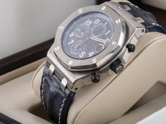 Wrist watch in open wooden box.