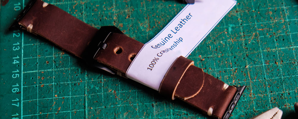 Leather watch strap craftsmanship working with white label on green board