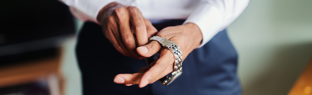 Close up of man putting watch on his hand.