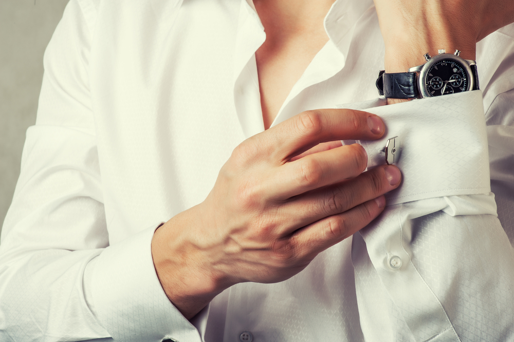 Man buttons cuff-link with watch on wrist