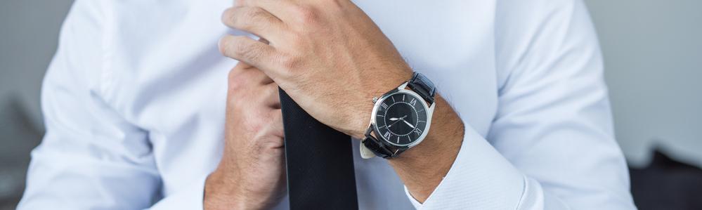 man-checking-tie-wearing-watch