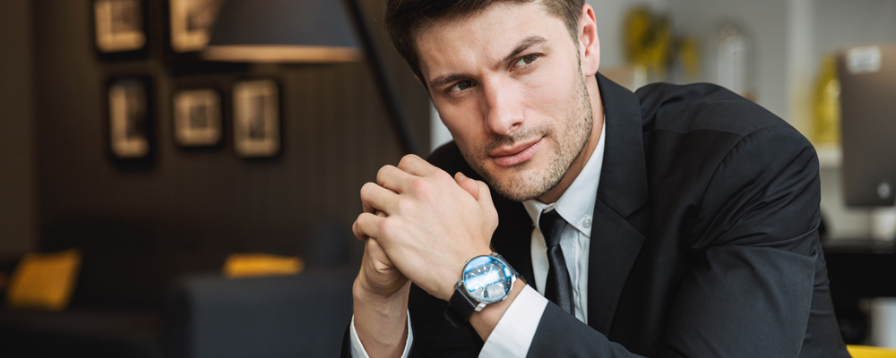Portrait of confident young businessman wearing formal black suit and wristwatch sitting on armchair in hotel hall