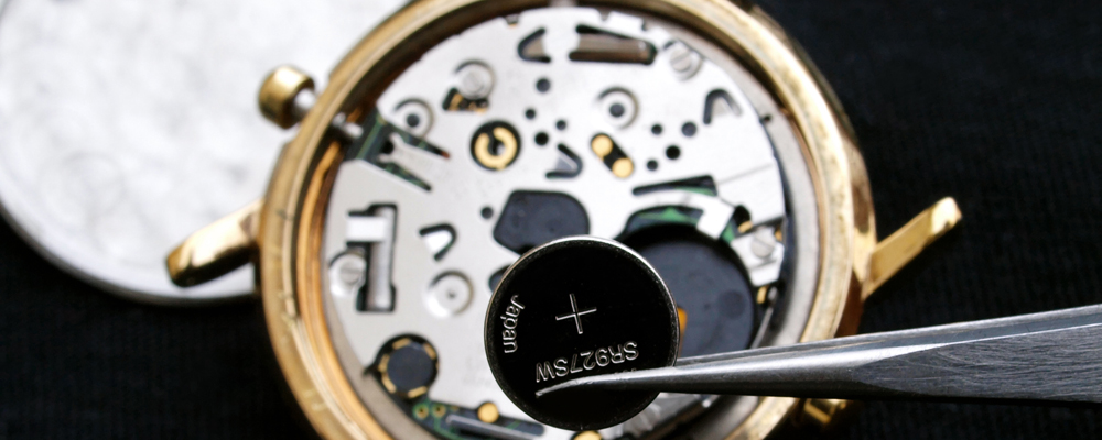 watchmaker change battery, close up of battery and quartz watch caliber in the background