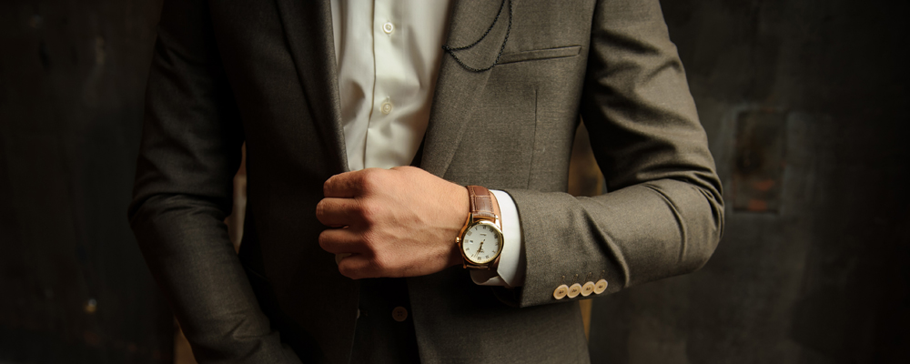 Close-up photo of a man with gold watch with a leather belt, dressed in a stylish gray suit, a white shirt and white bow.
