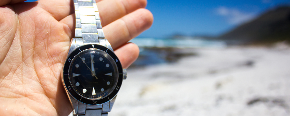 Man Holds A Steel Dive Watch At The Beach During Summer