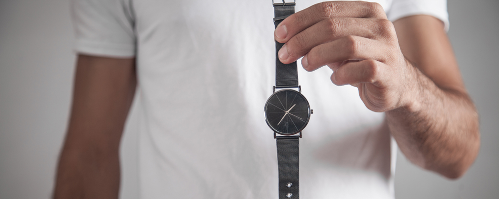 Caucasian man holding wrist watch in office.