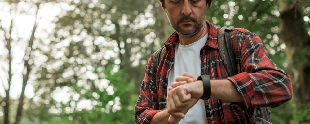 Smart watch on male hiker hand while hiking in the woods, selective focus