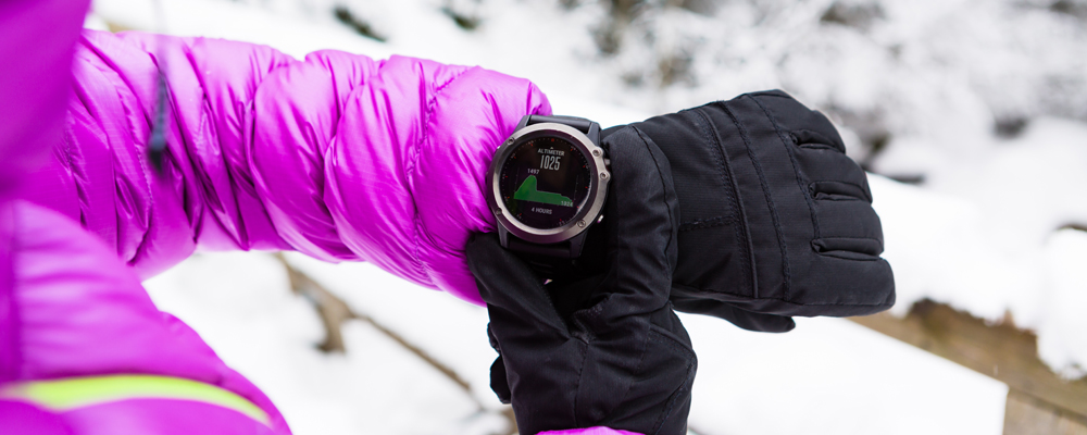 Woman hiker checking the elevation on sports watch, smartwatch with altimeter app in winter woods and mountains. Female trekker trekking in white snowy forest with electronics wearable technology.